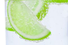 Pieces of fresh juicy lime sink into crystal clear water. stock image