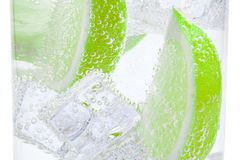 Pieces of fresh juicy lime sink into clear water with ice. royalty free stock photo