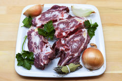 Pieces of fresh lamb on the plate . Delicious fat-tailed lamb with onion on the plate . Meat to be grilled. Stock Photos