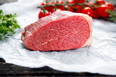 A pieces of fresh meat, beef slab, decorated with greens and vegetables.  Royalty Free Stock Photos