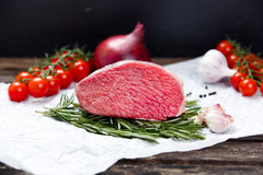 A pieces of fresh meat, beef slab, decorated with greens and vegetables. A pieces of fresh meat, beef slab, decorated with greens and vegetables Royalty Free Stock Photos