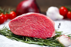 A pieces of fresh meat, beef slab, decorated with greens and vegetables. royalty free stock photo