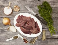 Pieces of fresh raw beef liver, onion, garlic, spices, dill, parsley, salt, knife, olive oil on porcelain plate on a wooden backgr Stock Photos