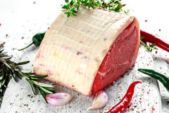 A pieces of fresh raw meat, beef slab, decorated with greens and vegetables. A pieces of fresh raw meat, beef slab, decorated with greens and vegetables Royalty Free Stock Photo