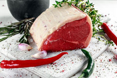 A pieces of fresh raw meat, beef slab, decorated with greens and vegetables. Stock Photography
