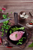 Pieces of fresh raw meat in a frying pan. Pork steak in a frying pan with herbs and spices on a wood table Stock Photography