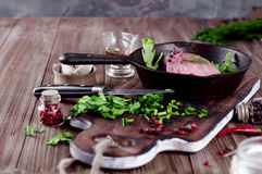 Pieces of fresh raw meat in a frying pan. Pork steak in a frying pan with herbs and spices on a wood table Royalty Free Stock Images