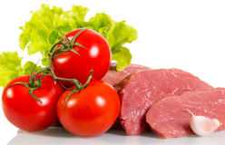 Pieces  fresh raw meat, tomatoes and lettuce  on white. Royalty Free Stock Image