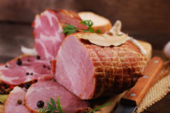 Pieces of fresh smoked ham on rural background Stock Photos