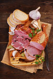 Pieces of fresh smoked ham on rural background Royalty Free Stock Photo