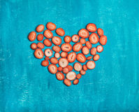 Pieces of fresh strawberry placed in heart shape, blue background Stock Photography