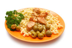 Pieces of fried chicken, pasta and parsley Stock Photos