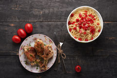 Pieces of fried chicken with vegetables and pasta on a able Royalty Free Stock Photo