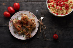 Pieces of fried chicken with vegetables and pasta on a able Royalty Free Stock Photos