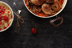 Pieces of fried chicken with vegetables and pasta on a able Stock Photography