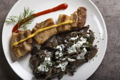 Pieces of fried fat pork meat with mushrooms and sour cream. On plate Stock Photography