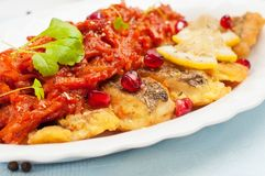 Pieces of fried fish with vegetable sauce. Royalty Free Stock Photo