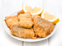 Pieces of fried hake dish with lemon. On wooden Stock Photography