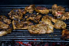 Pieces of fried meat on a grate, with smoke and fire. Fried meat on grate with smoke. royalty free stock images