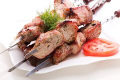 Pieces of fried meat on skewers, lying on white plate. Pieces of fresh fried meat on skewers, laying on a white plate with tomato and dill on white background Stock Photography