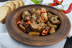 Pieces of fried pork with chilli in a clay bowl on a dark wooden background.  Stock Photos