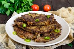 Pieces of fried pork liver on a plate. On a dark wooden background Royalty Free Stock Image