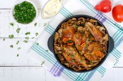 Pieces of fried rabbit with forest mushrooms on a cast-iron frying pan stock images