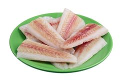 Pieces of frozen atlantic hake fish lying on a green plate isolated royalty free stock photos