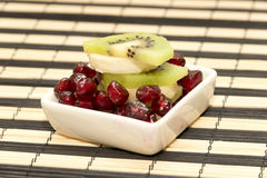 Pieces of fruit banana, kiwi, pomegranate in small platter Stock Images