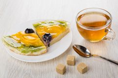 Pieces of fruit pie in plate, lumpy sugar, teaspoon, tea. Pieces of fruit pie in plate, lumpy sugar, teaspoon and cup of tea on wooden table Stock Images
