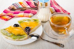 Pieces of fruit pie in plate, napkin, sugar, teaspoon, tea. Pieces of fruit pie in plate, napkin, sugar, teaspoon and cup of tea on wooden table Royalty Free Stock Photography