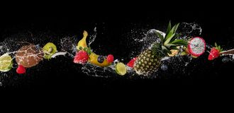 Pieces of fruit in water splash, isolated on black background. Pieces of fruit with mint leaves and ice cubes, falling in water splash, isolated on black stock images