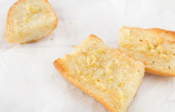 Pieces of garlic bread made with baguette on white paper Royalty Free Stock Image