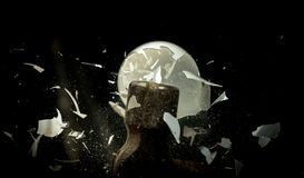 Shards of glass come off of a smashing light bulb as they hit a. Pieces of glass fly around from a light bulb hitting a hammer royalty free stock photos