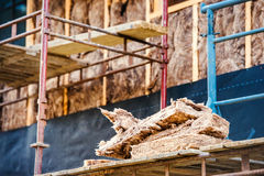 Pieces of glass insulation wool on scaffold against house Royalty Free Stock Image