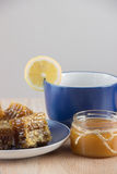 Pieces of golden honey comb on a table with tea, lemon and cinna Stock Photos