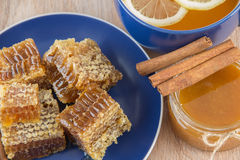 Pieces of golden honey comb on a table with tea, lemon and cinna Stock Images