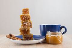 Pieces of golden honey comb on a table with tea, lemon and cinna Stock Photography