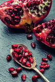 Pieces and grains of ripe pomegranate. Pomegranate seeds. Part of pomegranate fruit on granite board and antique spoon. Mediterran. Ean fruit Royalty Free Stock Photography