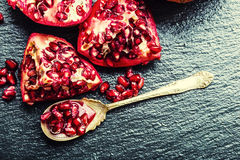 Pieces and grains of ripe pomegranate. Pomegranate seeds. Part of pomegranate fruit on granite board and antique spoon. Stock Image