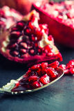 Pieces and grains of ripe pomegranate. Pomegranate seeds. Part of pomegranate fruit on granite board and antique spoon. Royalty Free Stock Photos