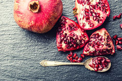 Pieces and grains of ripe pomegranate. Pomegranate seeds. Part of pomegranate fruit on granite board and antique spoon. Royalty Free Stock Images