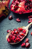 Pieces and grains of ripe pomegranate. Pomegranate seeds. Part of pomegranate fruit on granite board and antique spoon. Stock Photo