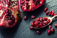 Pieces and grains of ripe pomegranate. Pomegranate seeds. Part of pomegranate fruit on granite board and antique spoon. Royalty Free Stock Photography