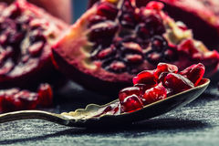 Pieces and grains of ripe pomegranate. Pomegranate seeds. Part of pomegranate fruit on granite board and antique spoon. Mediterranean fruit stock images