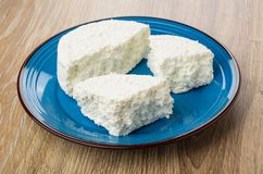 Pieces of grainy cottage cheese in blue plate on table Stock Image