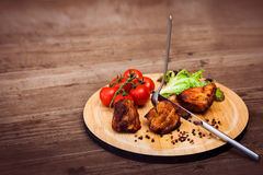 Pieces of grilled pork. Served with tomatoes on the branch and lettuce on a circular wooden board, knife is cutting meat. Horizontal Stock Images
