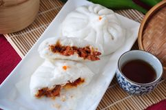 Pieces of Half Pork Bun on Plate. Pieces of half red pork bun on white plate Stock Images