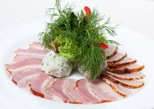 Pieces ham and bacon on a white plate Stock Images
