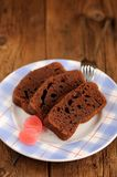 Pieces of homemade chocolate cake with pink candies on wooden ba Royalty Free Stock Photography